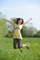 Happy young woman jumping on a meadow in spring, Germany