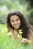 Young woman lying on a meadow beside cowslips in spring, Germany
