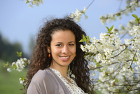 Portrait of a young woman with dark, curly hair standing beside a flowering cherry tree in spring, Germany