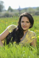 Young woman lying on a flowering meadow in spring, Germany