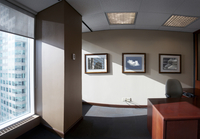 Interior of vacant office with desk, chair, and framed photographs on wall