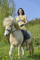 Young woman riding an icelandic horse on a meadow in spring, Germany
