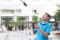 Boy playing with a remote control helicopter in an urban park.
