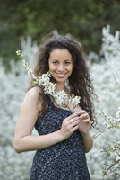 Close-up of a young woman holding a flowering blackthorn branch in her hands in spring, Germany
