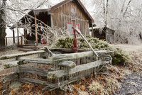 Aftermath of April Spring Ice Storm, Water Pump and House Covered in Ice , near Madoc, Ontario, Canada