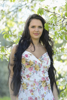 Portrait of a young woman standing beside a flowering cherry tree in spring, Germany