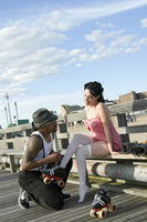 A man helping a woman put on rollerskates on the boardwalk in Coney Island New York