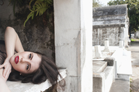 A woman laying inside an empty tomb in a new orleans graveyard