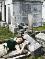 A young woman laying on grave stone in a cemetery, New Orleans, Lousiana, USA