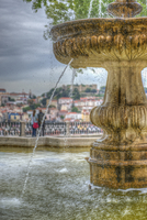 Close-up view of the  fountain at the Miradouro Sao Pedro lookout, overlooking Lisbon. A couple is in the background taking in t
