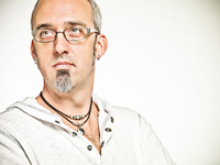 portrait of man with salt and pepper hair, glasses, and a goatee wearing a white pullover shot on a white background.