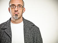 portrait of man with salt and pepper hair, glasses, and a goatee wearing a white t-shirt and winter coat shot on a white backgro