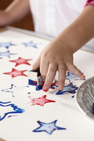 Close-up of child's hand stamping star-shapes in paint on a sheet of paper