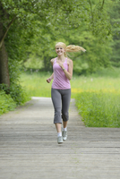Blond woman running outdoors on wooden footpath, Germany
