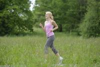 Blond woman running through field, Germany