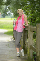 Portrait of blond woman wearing exercise clothing and holding bottle of water outdoors, Germany