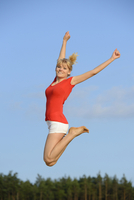 Young Woman Jumping in the Air in Summer,  Bavaria, Germany