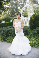 Portrait of Bride standing outdoors in front of white fence and gate, Ontario, Canada