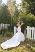 Bride and Groom standing outdoors next to fence on Wedding Day, looking at camera