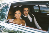 Portrait of Bride and Groom sitting in backseat of car on Wedding Day, looking at camera