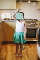 Young girl holding dustpan in front of face, standing in kitchen.