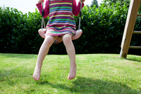 Girl sitting on a swing in backyard