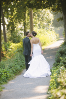 Backview of Bride and Groom kissing and holding hands, walking down pathway outdoors, on Wedding Day