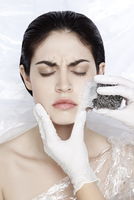 Woman with eyes closed wrapped in plastic, with hands in latex glove scrubbing face with scourng pad, studio shot