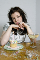 Woman sitting at table with cupcake and candle and glass of champagne, absorbed in thought, USA
