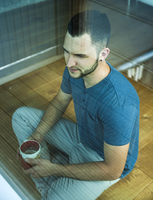 Young Man Sitting on Floor with Coffee Cup, Mannheim, Baden-Wurttemberg, Germany