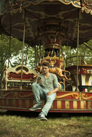 Young Man using Cell Phone while Sitting on Edge of Carousel, Mannheim, Baden-Wurttemberg, Germany