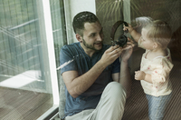 Baby Girl and Father with Headphones at Home, Mannheim, Baden-Wurttemberg, Germany