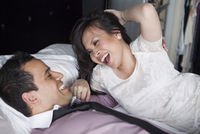 Close-up of couple laying on bed laughing