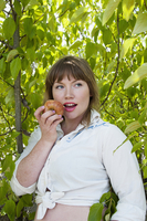 Close-up portrait of woman eating an apple, standing in front of a tree