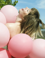 A woman holding a bunch of pink balloons