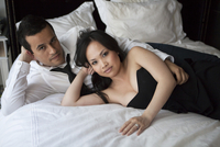 Portrait of couple laying on bed in formal wear, looking at camera