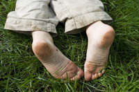 Dirty Feet of Boy Lying in Grass, New Jersey, USA