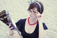 Portrait of young woman wearing horn-rimmed eyeglasses reading magazine on beach, Italy