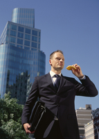 Businessman Eating Waffle on way to Work, New York City, New York, USA