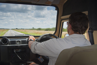 Man driving vehicle on road to Etosha, Namibia, Africa