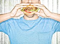 Close-up of Man eating Cheeseburger, Studio Shot