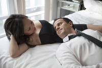 Couple laying in bed wearing formal wear, looking at each other