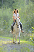 Portrait of young woman riding a white, Bavarian Warmblood horse, Bavaria, Germany