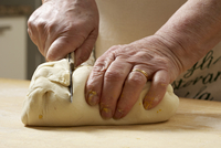 Close-up of elderly Italian woman making pasta by hand in kitchen, working with dough, Ontario, Canada