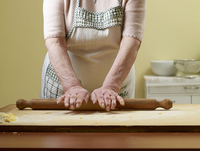 Elderly Italian woman making pasta by hand in kitchen, rolling dough, Ontario, Canada