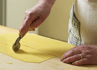 Close-up of elderly Italian woman making pasta by hand in kitchen, cutting pasta dough with rotary tool, Ontario, Canada