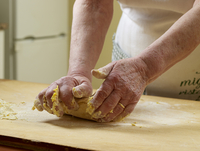 Close-up of elderly Italian woman's hands kneading pasta dough in kitchen, Ontario, Canada