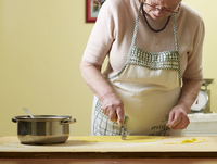 Elderly Italian woman making pasta by hand in kitchen, working with dough, Ontario, Canada