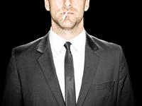 Mid Adult Man in Suit, Smoking Cigarette, Studio Shot