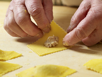 Close-up of elderly Italian woman's hands making ravioli pasta in kitchen, adding filling, Ontario, Canada